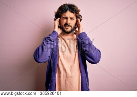 Young handsome sporty man with beard wearing casual sweatshirt over pink background covering ears with fingers with annoyed expression for the noise of loud music. Deaf concept.