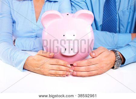 Couple with a piggy bank. Saving money.