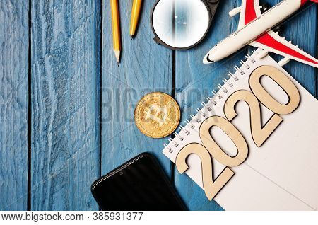 2020 And Notebook With Pen, Wooden Bitcoin, Smartphone And Model Of A Toy Airplane On A Blue Wooden