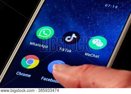 Close Up View Of Tiktok And Wechat Logo, App Icon Displayed On A Smartphone With Finger, Trump Banne