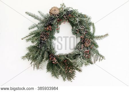 Creative Stylish Christmas Wreath With Red Berries And Fir Branches, Isolated In White