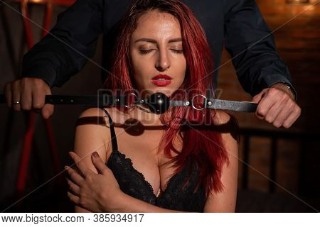 A Man Puts A Gag In His Partners Mouth During Role Play