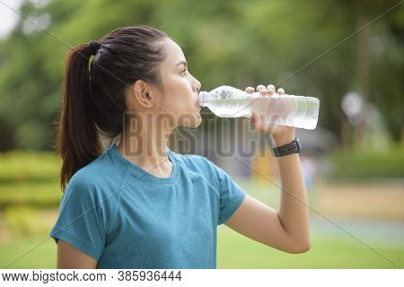 Fitness Woman Is Drinking Water After Workout In Park