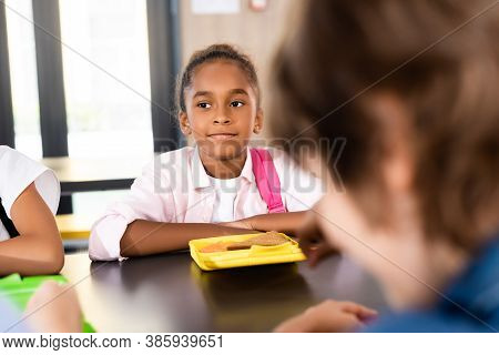 Selective Focus Of African American Schoolgirl Sitting In School Eatery Near Lunch Box