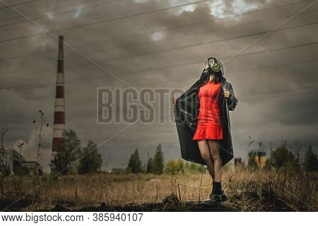 Woman In Gas Mask, Red Dress And In The Raincoat Is Standing On The Smoking Chimney Background.