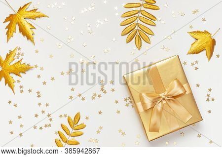 Flat Lay Autumn Holiday Concept. Golden Gift Or Present Box With Ribbon, Confetti Stars, Golden Autu