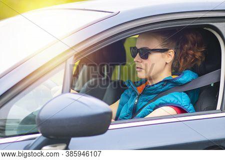 A Woman Drives A Car, A Female In A Traffic Jam In Sunglasses