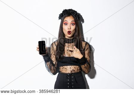 Surprised Asian Girl In Black Gothic Dress With Wreath, Gasping Amused And Pointing Finger At Mobile