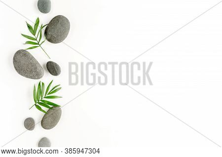 Spa Stones, Palm Leaves, Candle And Zen Like Grey Stones On White Background. Flat Lay, Top View