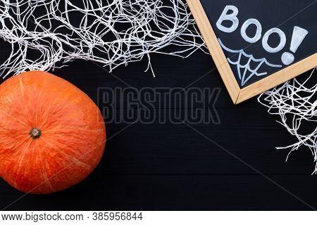 Orange And Black Halloween Flatlay. Chalk Inscription Boo, Pumpkin And Spider Web On Black Wooden Ba