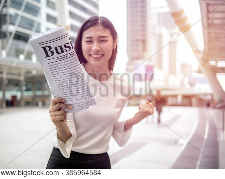Excited Woman Holding A Newspaper At City Park Background, Good News