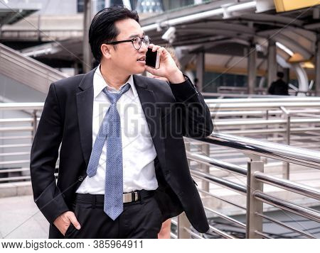 Business Man Walking In The Corridor Talking On The Phone Of An Business Center.