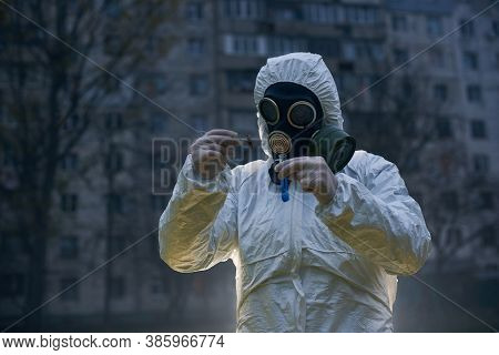Ecologist Wearing Gloves, White Coverall And A Gas Mask, Holding A Glass Flask With Blue Liquid And