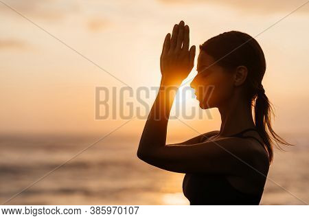 Yoga At Sunset On The Beach. Woman Performing Asanas And Enjoying Life On The Ocean. Bali Indonesia.