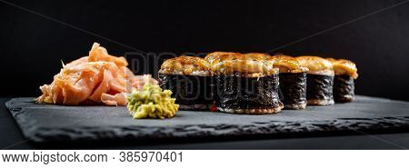 Panoramic Photo Of Served Warm Sushi Rolled In Nori Sheets With Ginger And Wasabi On A Black Stone P