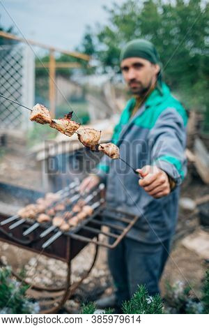 A Man Fries Kebabs On The Grill In His Infield. Close-up, Selective Focus.