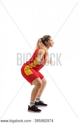 Full length profile shot of a young female defence basketball player in action isolated on white background