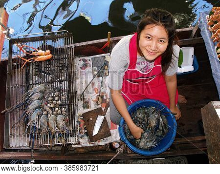 Bangkok, Thailand, September 26, 2015: A Girl Grills Seafood On The Barbecue Of Her Boat At The Tali