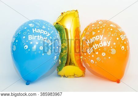Inflatable Numeral 1 Sparkling Metallic Golden Color With Blue And Yellow Balloons Isolated On White