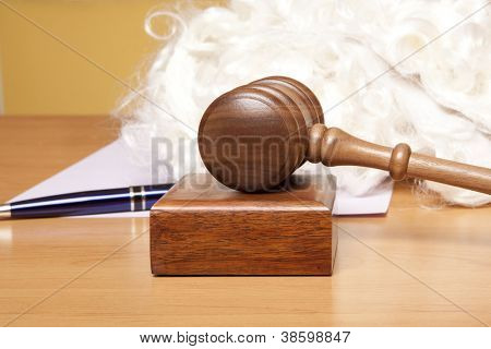 Gavel, judge's wig and pen on the table