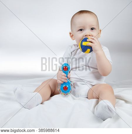 Shot Of A Ten-month-old Baby With Rattle And Ball