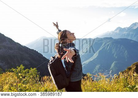 Backpacker In The Mountains In Awe Of Nature Embraces The World. Young Woman On A Mountain Hike