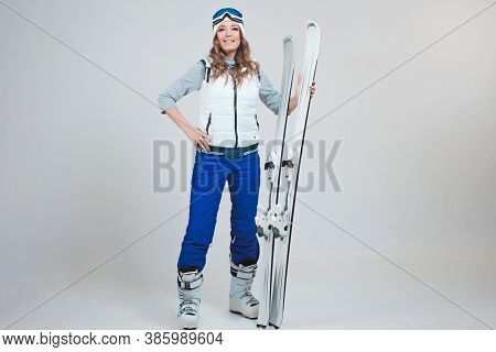Smiling Woman Skier In A Hat And Mask For Skiing. A Young Woman In Clothes For Skiing And Outdoor Ac
