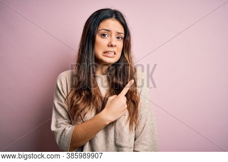 Young beautiful brunette woman wearing casual sweater standing over pink background Pointing aside worried and nervous with forefinger, concerned and surprised expression