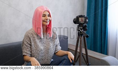 Young And Smart. Beautiful Young Woman With Pink Hair In Casual Wear While Recording Video Blod