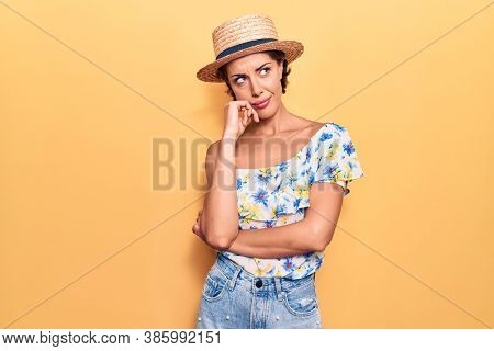 Young beautiful woman wearing summer hat thinking concentrated about doubt with finger on chin and looking up wondering