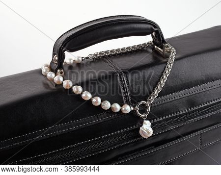 Women`s Silver Baroque Pearl Necklace With Pendant On Male Black Leather Briefcase. Close-up Shot