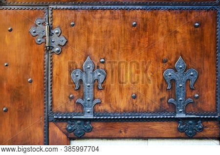 Plain Old Red Wooden Surface With Ancient Metal Decorated Hinges On The Door Of A Traditional Tuscan