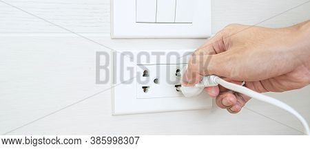 Closeup Male Finger Unplugging Or Plugging Of Electricity Device On White Wall At Home. Energy Savin