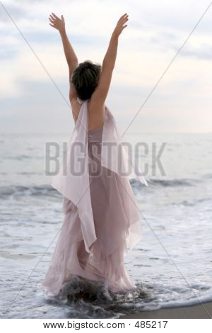 Woman In Pink Dress On The Beach