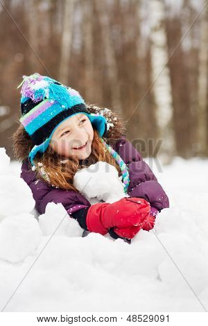 Laughing rosy girl in jacket, knitted hat and mittens lies on snowdrift