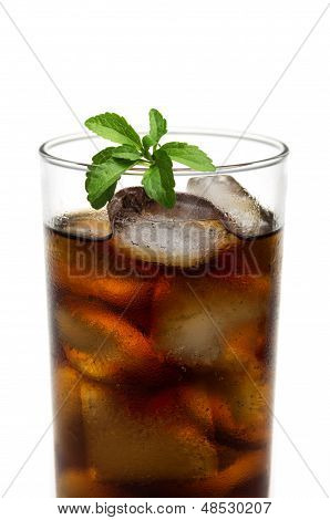 cola in glass with stevia leafs on a white background