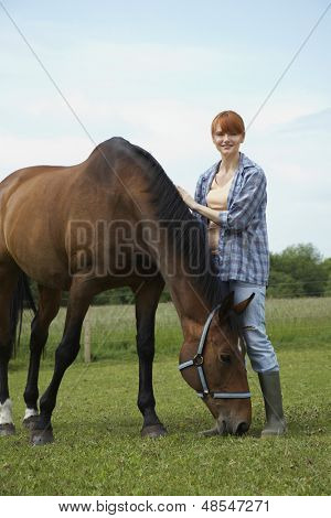 Full length portrait of a smiling woman with horse in field poster