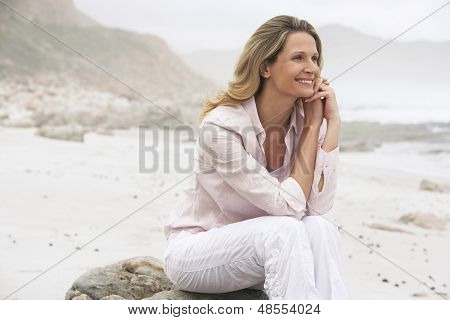 Happy woman looking away while relaxing on rock at beach