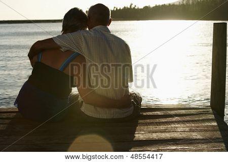 Vista posterior de la feliz pareja senior, sentado en el borde del muelle en el lago