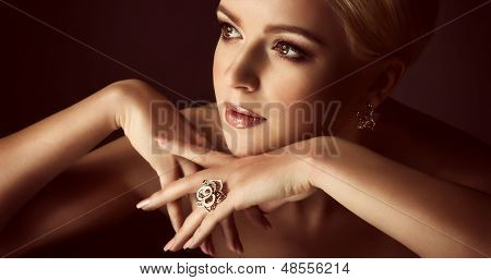 Portrait of beautiful young woman with jewelry on black background