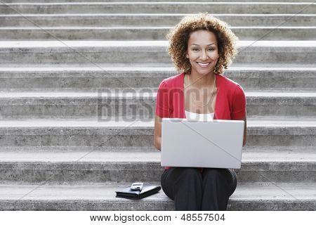 Portrait of a smiling young African American woman using laptop on steps outdoors