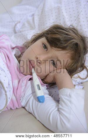 sick girl lying in bed measuring fever