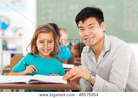 caring elementary school teacher helping student in classroom poster