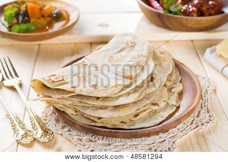 Chapatti roti or Flat bread, curry chicken and dhal. Indian food on dining table. poster