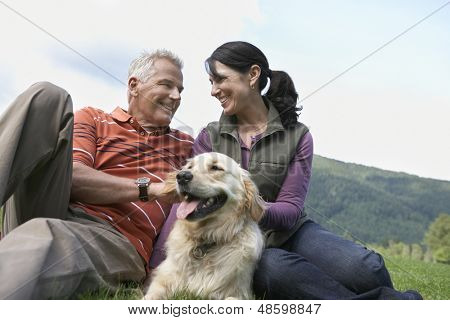 Happy middle aged couple and golden retriever relaxing on grass