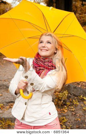 young beautiful autumn woman under umbrella