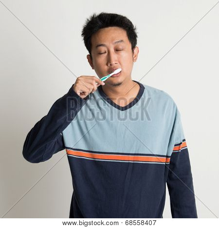 Sleepy Southeast Asian male brushing teeth while eyes closing in a morning, on plain background