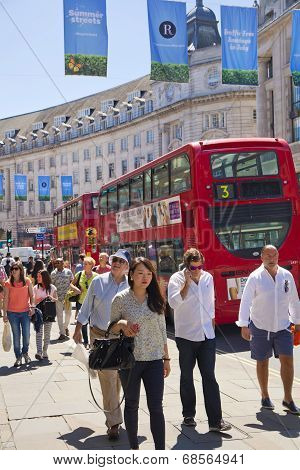 LONDON, UK - JUNE 3, 2014: Regent street, tourists and red double decker bus. regent street on of th