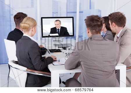 Group of business people in video conference at meeting table poster