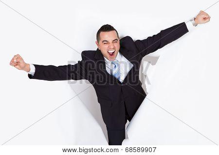 Successful Businessman Breaking Through White Wall